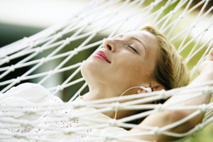 Close up portrait of an attractive blonde woman laying down on a hammock listening to music, with her eyes closed and smiling.